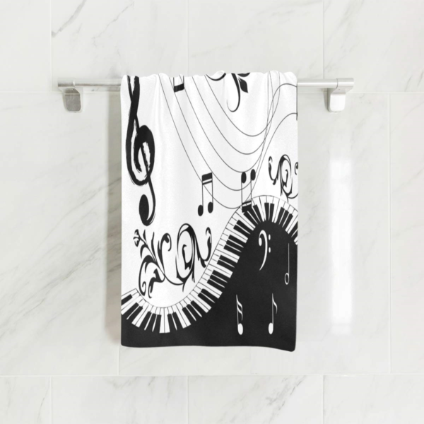 A Black & White Bath Towel that is hanging up and has Music Notes & Floral Piano Keys on it